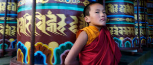 Bhutanese child monk leans against colourful columns at a monastery