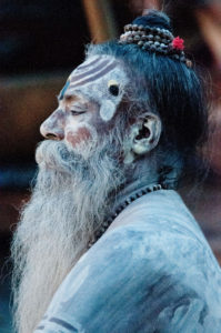 Holy man in India with traditional face paint and accessories