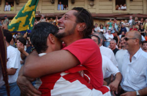 Two men hugging each other at Siena's horserace