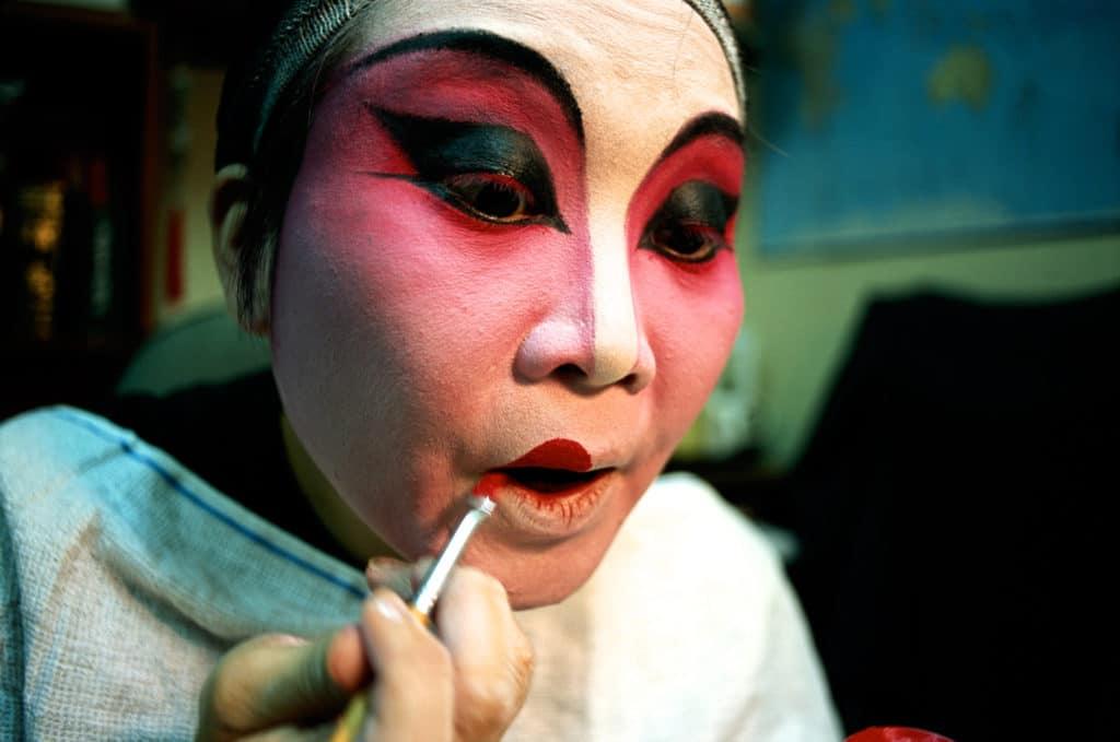A Bhutanese woman applies traditional face paint