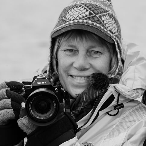 Black and white image of Better Moments Expert Sisse Brimberg with her camera