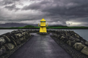 A lone yellow lighthouse on a cloudy day in Iceland's capital Reykjavik