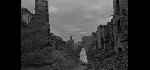 Veiles woman walks through ruins, Afghanistan