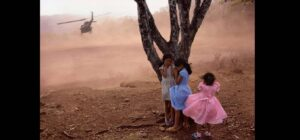 Three girls hiding from a helicopter behind a tree, El Salvador