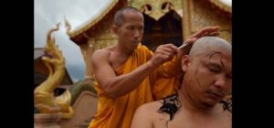Thai monk shaves another monk's head