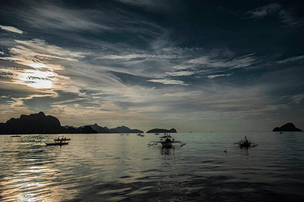 Boats are floating in the calm waters next to Palawan, Philippines.
