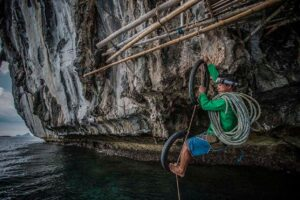 A pearl hunter climbs down a steep cliff on Flower Island, Philippines.