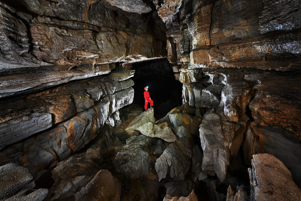 A women stands in Krizna Cave illuminated by strobe light
