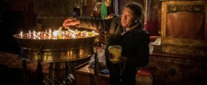 Buddhist Pilgrims light candles in one of the many and historic temples of Tibet Lhasa, China.