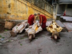 Two child monks and a buddha statue in Burma
