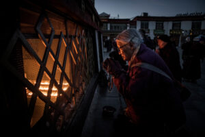 Woman praying early in the morning at Jokhang Temple, Christian Nørgaard and Christian Noergaard in Lhasa, the Most Sacred and Important city in Tibetan Buddhism. A Better Moments Workshop in Tibet, China and nepal kathmandu.
