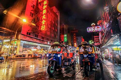 A row of tuktuk is waiting for passengers udnerneath the city's neon signs