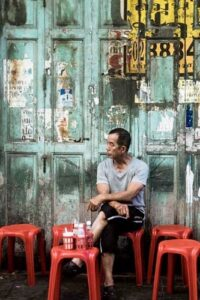 A man is waiting for his food order in one of the many street kitchens