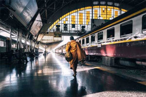 A monk in a yellow robe walks to his train