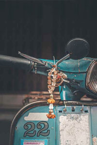 Blue vintage scooter with beads wrapped around the handle bar