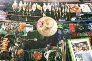 A woman is selling fresh fish and vegetables from her tiny stall