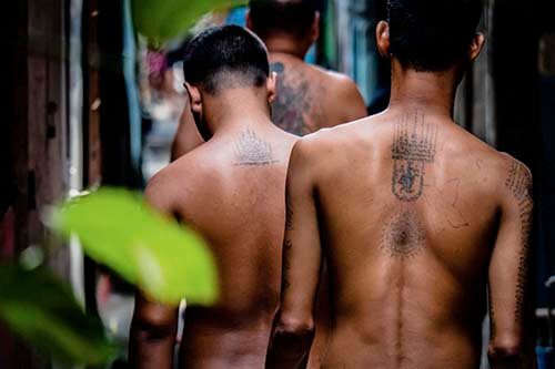 Three Thai with tatooes on their back walk through an alley way