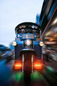 A tuktuk coming at the viewer at full speed