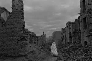 A woman wrapped in white walks through her destroyed home town
