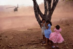 Three girls hiding behind a three as a helicopter takes off