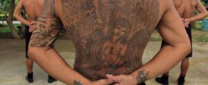 Man with back tattoo standing with hands crossed behind his back