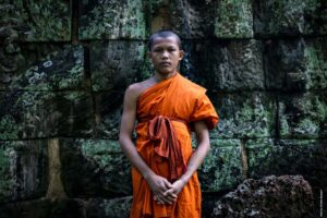 Monk in bright orange robe stands in front of the green ruins of Angkor Wat