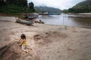 Christian Nørgaard Better Moments Indochina - girl playing at Mekong River - Laos