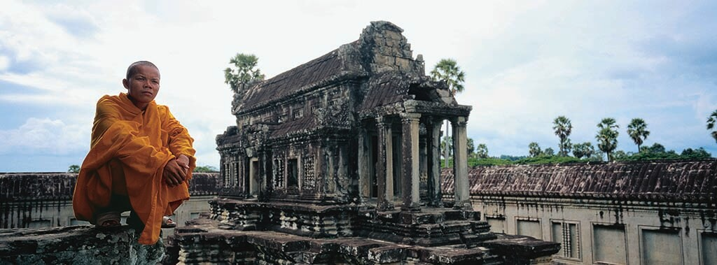 Monk in an orange-colored robe sits on the ruins of Angkor Wat, Cambodia