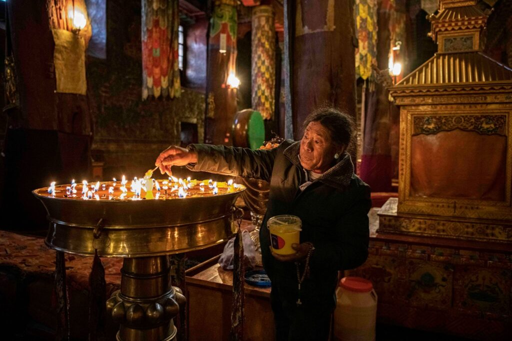An elderly man lights candles in a Tibetian monastery