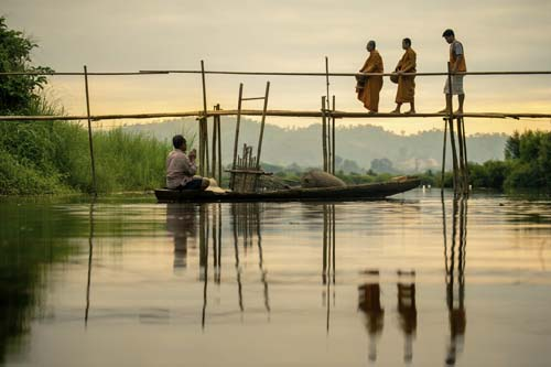 Monks are crossing a bridge with a fisherman watching