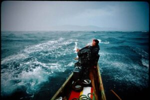 Man in a tiny boat on the stormy sea