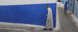Elderly man dressed in white walks along a blue-painted wall