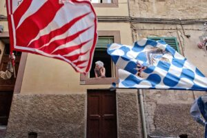 Old woman watching the Il Palio the Siena spectacle from her window