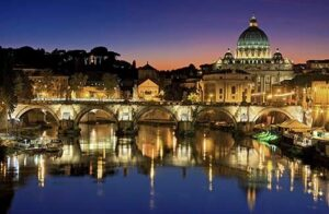 Illuminated buildings of Rome reflecting in river Tiber