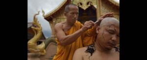 Thai monk is getting his head shaved
