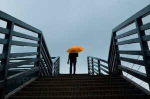 Man with an organge umbrella stands at the top of a stairway