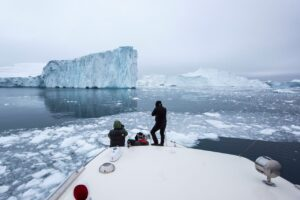 Photographers sitting on the stern of a ship to photograph icebergs