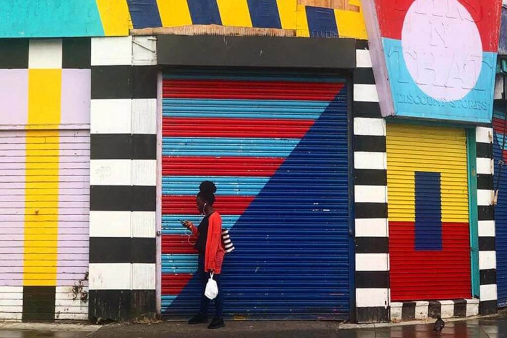 Woman walks in front a colourful storefront in Hackney, London
