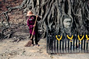 Thai woman with a broom Thai Elepephant driver and his elephant by Steve McCurry